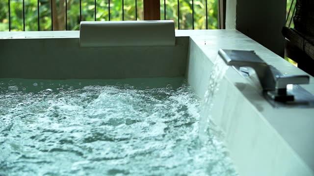 浴室で渦巻く水の白い正方形ジャグジー。 - ジャクジー点の映像素材/bロール