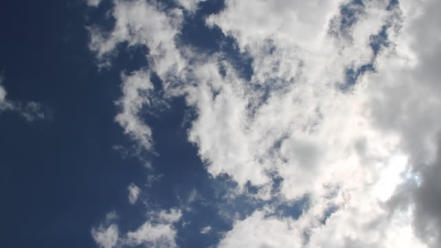 white stratus clouds float in a deep blue sky. - stratus stock videos & royalty-free footage