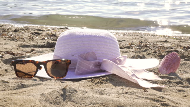white straw hat with a pink ribbon and sunglasses are on the sea shore - straw hat stock videos & royalty-free footage