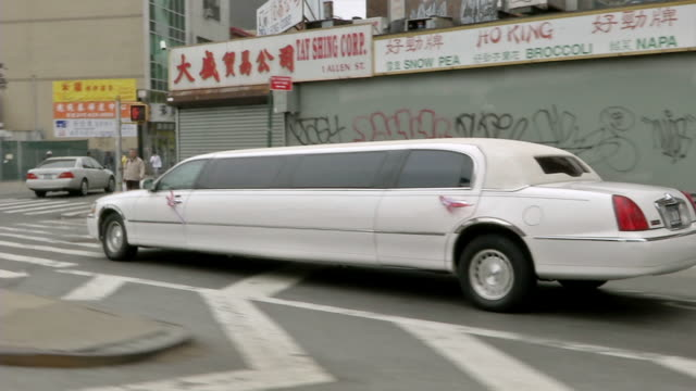 ms ts white stretch limosine driving through chinatown / new york, united states - limousine stock videos and b-roll footage