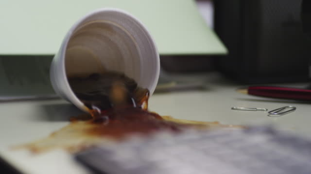 White styrofoam cup of black coffee is spilled on an office desk.