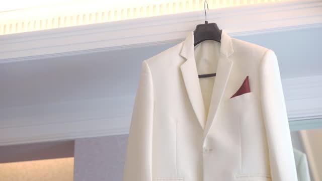 vidéos et rushes de costume blanc suspendu prêt pour le mariage - le marié