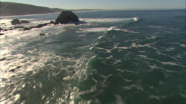 white surf crashes around rocks off a beach. - boulder rock stock videos & royalty-free footage