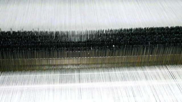 stockvideo's en b-roll-footage met witte draden op een weefgetouw in weven weefgetouw machine in textielfabriek - weven