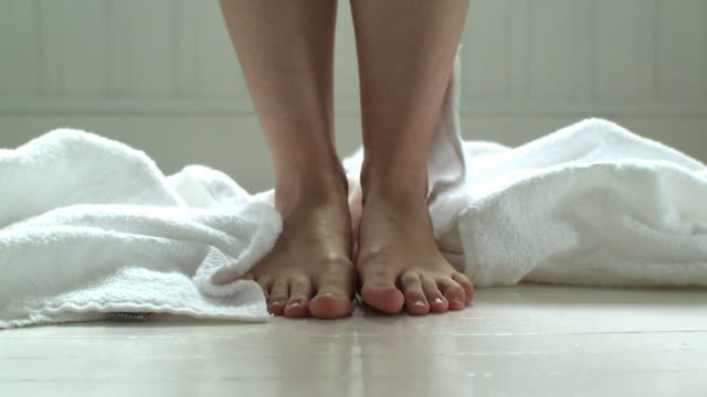 CU White towel falling at woman's feet on bathroom floor, Scarborough, New York, USA