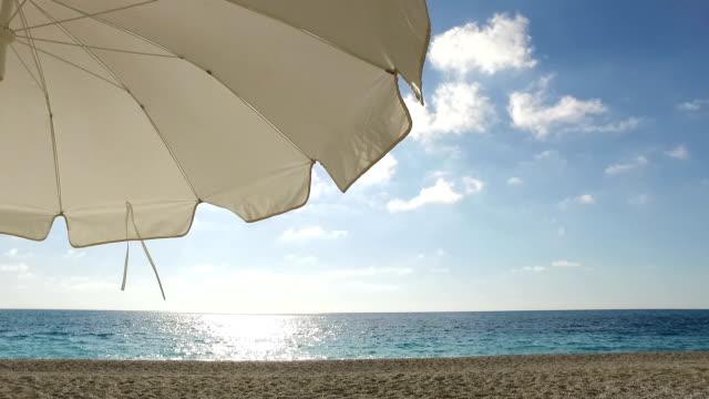 white umbrella and a blue ocean - beach umbrella stock videos and b-roll footage