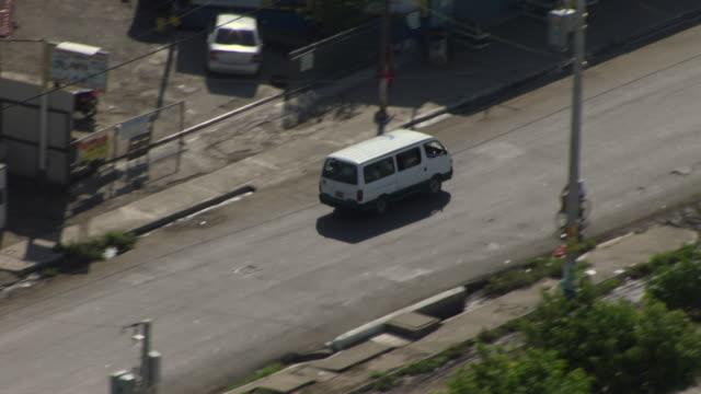 A white van passes through the city streets of Kingston, Jamaica.