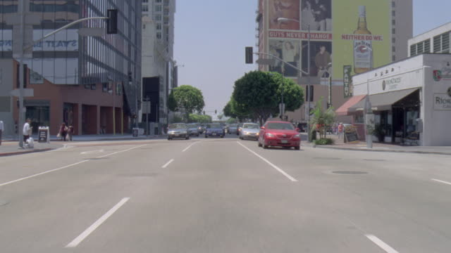 POV White van pulling in front of traffic driving on city streets / United States