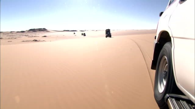 a white vehicle leads a convoy across the desert. - konvoi stock-videos und b-roll-filmmaterial