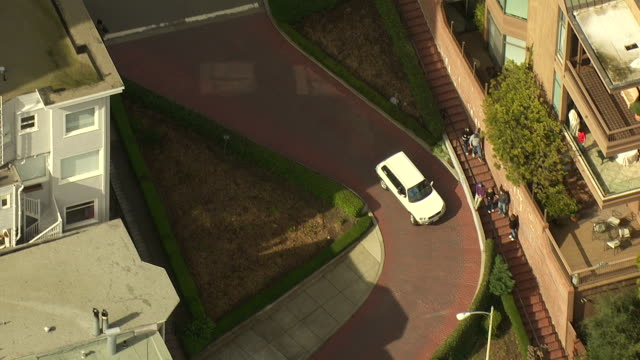 a white vehicle travels along lombard street in san francisco. - lombard street san francisco stock videos & royalty-free footage