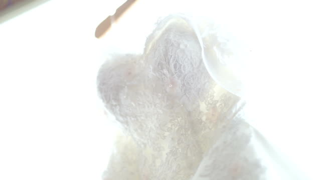 white wedding dress hanging in the room. - wedding dress stock videos and b-roll footage
