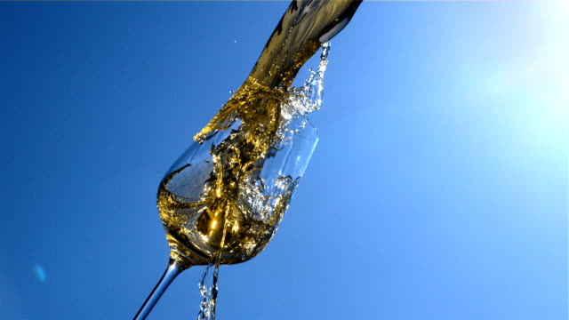 white wine is pouring in to a glass with blue sky and sunshine on background in slow motion - blue glass stock videos and b-roll footage