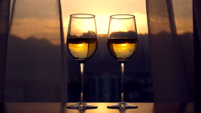 white wine on table at sunset - bicchiere da vino video stock e b–roll