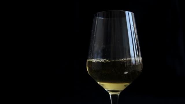 white wine pouring and swirling in glass - schwarzer hintergrund stock-videos und b-roll-filmmaterial