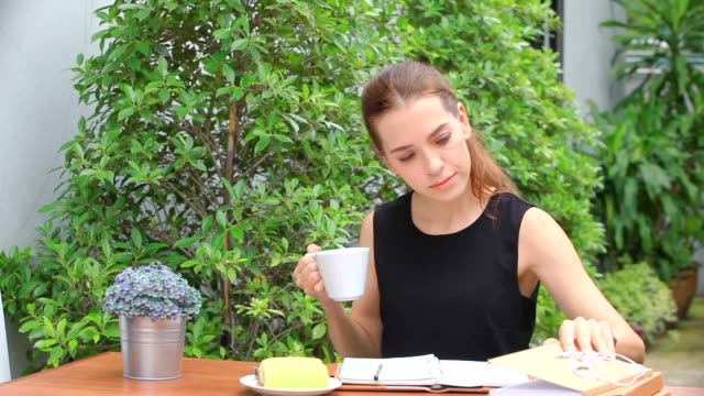 white women, russian ladies sit and drink coffee in the morning on a wooden table in the backyard. - coffee drink stock videos & royalty-free footage