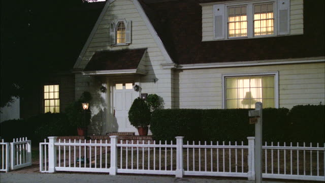 vídeos de stock, filmes e b-roll de ms white wood frame house with picket fence & lights on inside - cerca