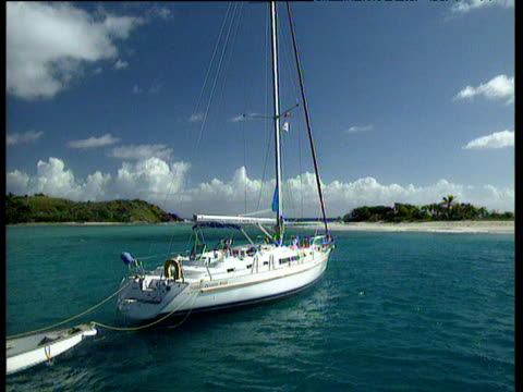 White yacht with small boat attached floats in turquoise sea with desert island in background British Virgin Islands.