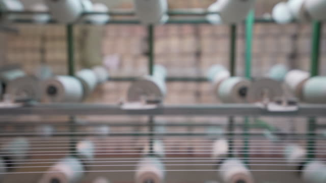 White yarn spools in warping creel of industrial warping machine in textile factory