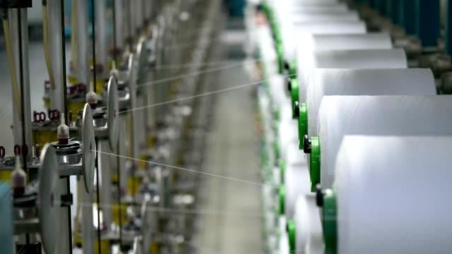 stockvideo's en b-roll-footage met witte garen spoolt voor industriële kromtrekken machine in textielfabriek - polyester