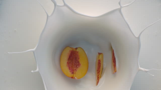 white yogurt with peach fruit falling down - yoghurt stock videos and b-roll footage