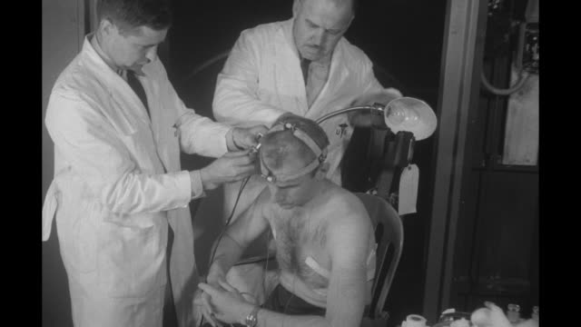 whitecoated james ziegler and charles gall attach wires to dr edward rackman's headgear he then dons jumpsuit and enters large metal spherical... - jumpsuit stock videos and b-roll footage