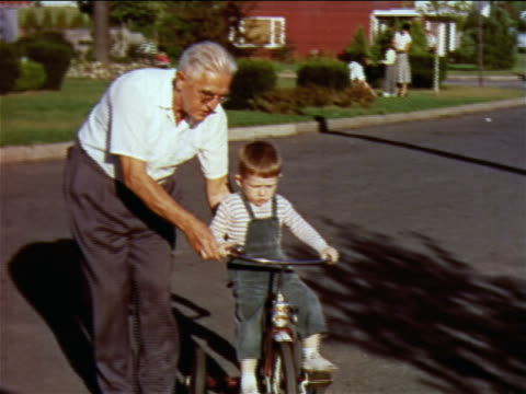 stockvideo's en b-roll-footage met 1957 white-haired man helping young boy ride tricycle in street / new jersey / industrial - 1957