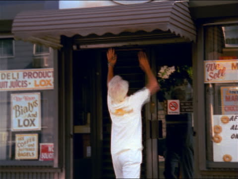 white-haired man lowering metal gate over front of bagel shop / nyc - bäckerei stock-videos und b-roll-filmmaterial