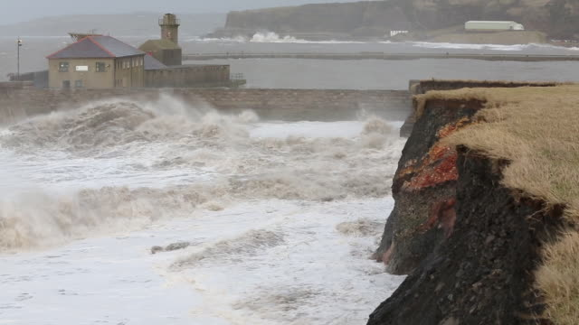 vídeos de stock, filmes e b-roll de whitehaven harbour and sea cliffs during the january 2014 period of storm surge, high tides and storm force winds. the coastline took a battering, damaging the harbour wall and eroding a large section of coastal cliff. - erodido
