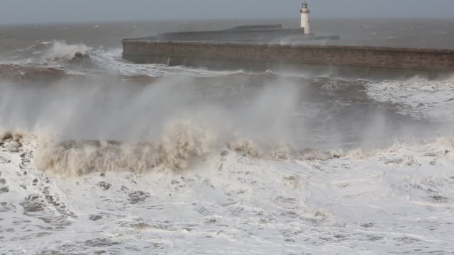 whitehaven harbour and sea cliffs during the january 2014 period of storm surge, high tides and storm force winds. the coastline took a battering, damaging the harbour wall and eroding a large section of coastal cliff. - ocean tide stock videos & royalty-free footage