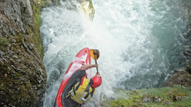 slo mo whitewater kayaker in a red kayak dropping a waterfall - extreme sports stock videos & royalty-free footage