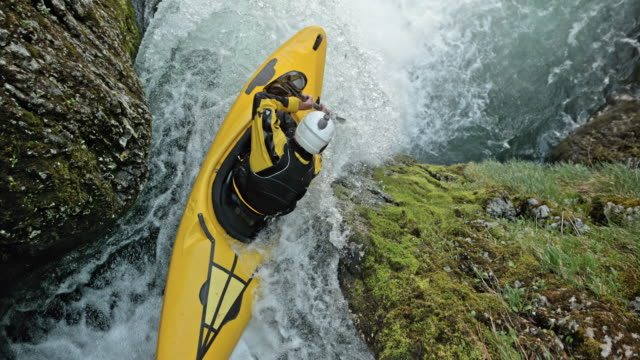 slo mo whitewater kayaker in a yellow kayak dropping a waterfall - kayak video stock e b–roll