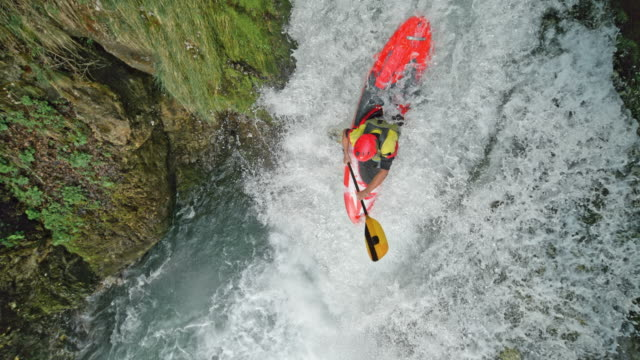 vídeos de stock e filmes b-roll de slo mo whitewater kayaker running a waterfall - kayaking