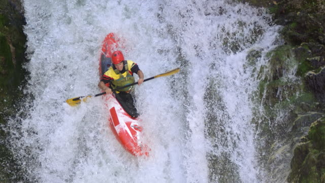 slo mo whitewater kayaker running down the waterfall and hitting the plunge pool - kayak video stock e b–roll