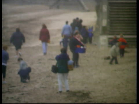 stockvideo's en b-roll-footage met whitley bay ext/itn children walking along windy beach wearing waterproof clothing / children wearing coats playing in the sand / children looking... - whitley bay
