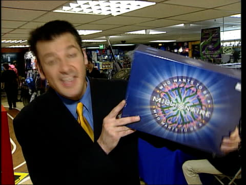 vídeos de stock, filmes e b-roll de 'who wants to be a millionaire?' board game; itn england: london: various board games on display people playing game i/c adrian woolfe interview sot... - television game show