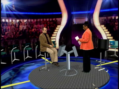 vídeos de stock, filmes e b-roll de who wants to be a millionaire trial: ingrams maintain innocence; itn gir: int ohajah and charles ingram sat in vrg mock-up of the 'who wants to be a... - game show