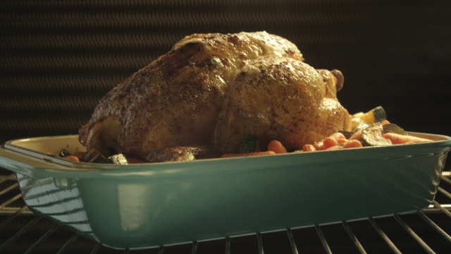 a whole chicken roasts in an oven as basting juices pour from a ladle. - oven stock videos & royalty-free footage