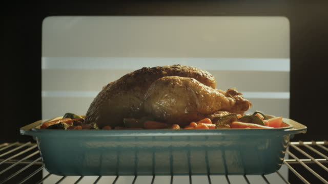 A whole chicken roasts in an oven.