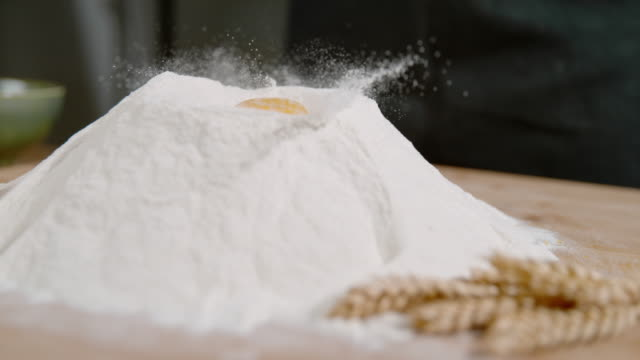 slo mo ds whole egg dropping into flour - egg yolk stock videos and b-roll footage