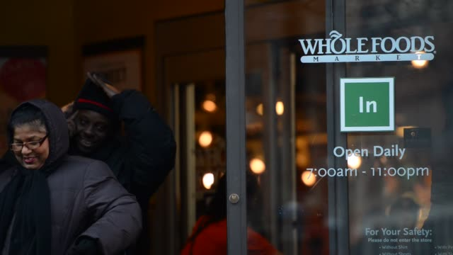 whole foods location in tribeca new york ny us on monday february 10 wide shot of a white couple wearing winter coats exiting whole foods close up of... - whole foods market stock videos and b-roll footage