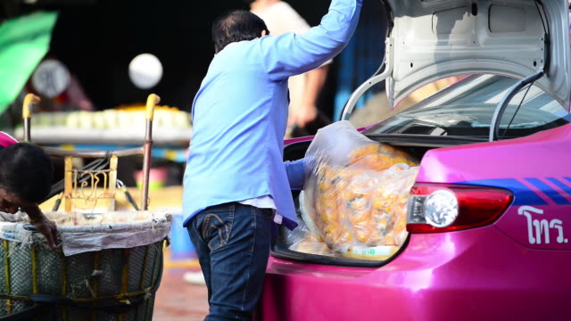 stockvideo's en b-roll-footage met wholesale flower are being loaded onto the boot of a taxi from flower market - taxi