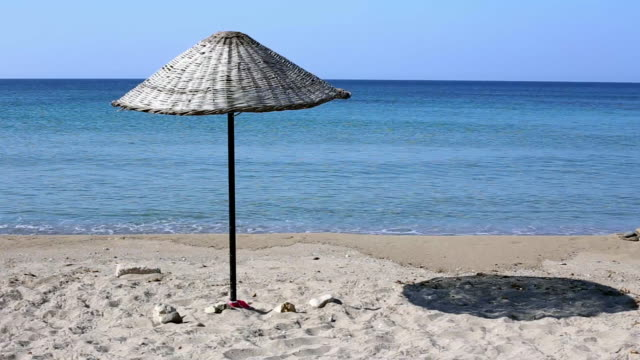 wicker umbrella on on izmir sand beach - wicker stock videos & royalty-free footage
