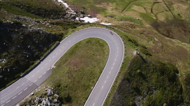 Wide aerial high angle shot of motorcycle and bicycle on mountain pass / Grossglockner, Austria