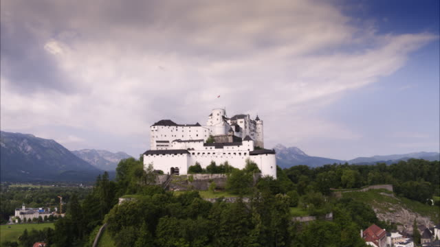 Wide aerial panning shot of fortress on hill / Salzburg, Austria