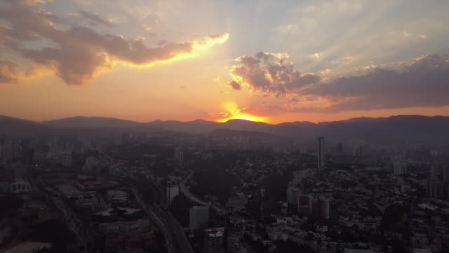 Wide aerial, scenic sunset over Mexico City skyline