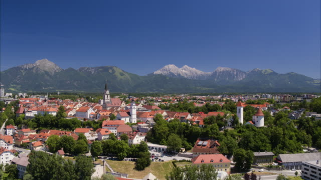 vídeos de stock, filmes e b-roll de wide aerial shot approaching village near mountain range / kranj, slovenia - kranj