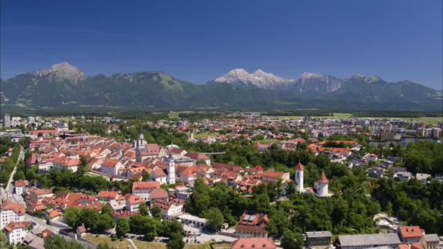 wide aerial shot approaching village near mountain range / kranj, slovenia - slovenia stock videos & royalty-free footage