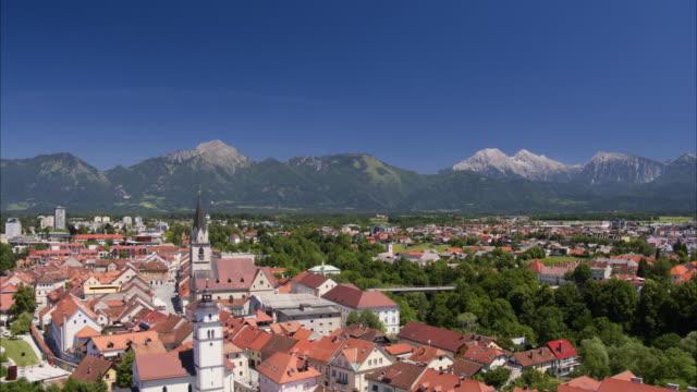 vídeos de stock, filmes e b-roll de wide aerial shot leaving village near mountain range / kranj, slovenia - kranj