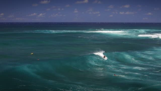 wide aerial shot of a young surfer riding inside the tube of a large wave - kahuku stock videos & royalty-free footage