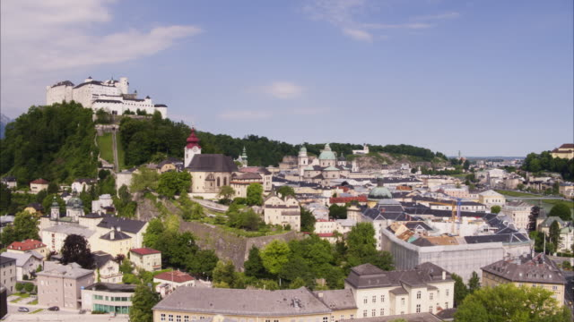 Wide aerial shot of fortress on hill in city / Salzburg, Austria
